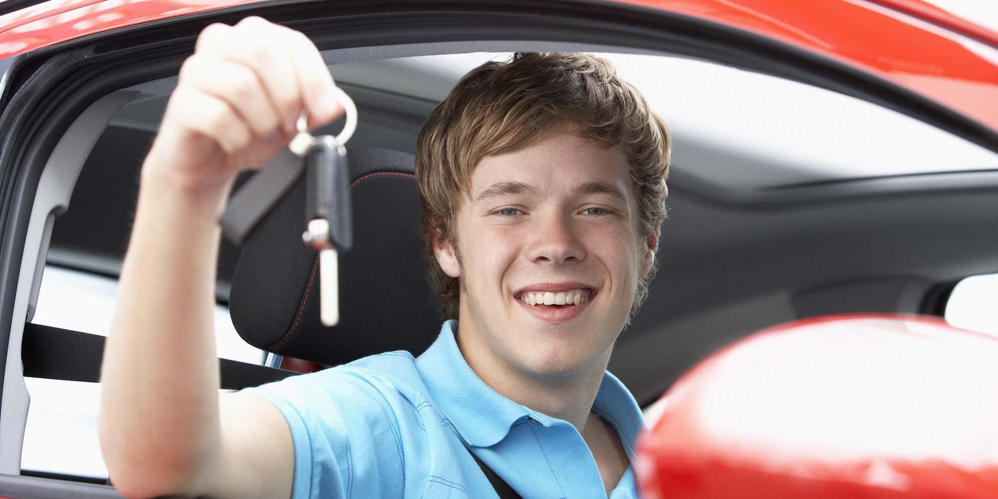Teenage boy holding car keys sitting in car